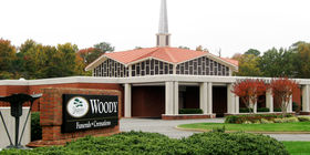 Front exterior building with signage at Woody Funeral Home Huguenot Chapel