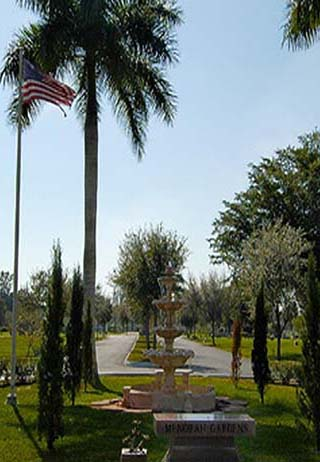 Street entrance with water fountain and palm trees at Menorah Gardens & Funeral Chapels.