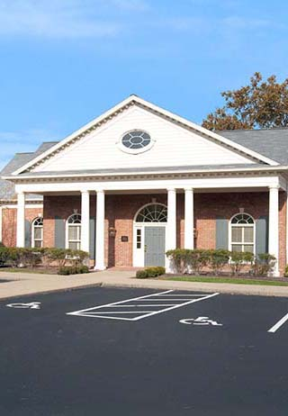 Front exterior building entrance with parking spots at Alexander Funeral Home-Newburgh Chapel.