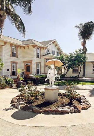 Front exterior building with a statue of a woman with an umbrella at Funeraria Del Angel Lincoln Heights.