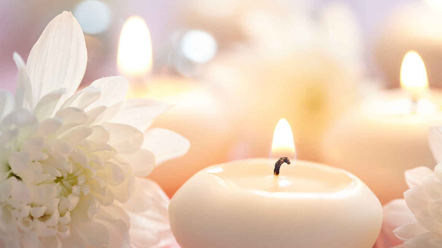 A serene setting of white candles and flowers evokes peace and tranquility.