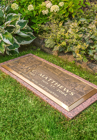 Bronze and granite flat marker in a private garden of hydrangeas.