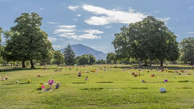 Cemetery grounds with flat markers and a view of the mountains at Wasatch Lawn Memorial Park.