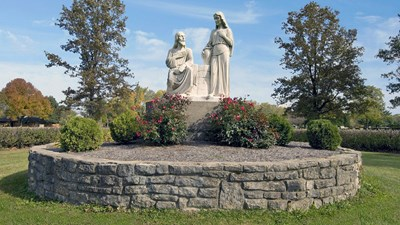 Man and woman at the well statue on a stone platform at Miami Valley Memorial Gardens.