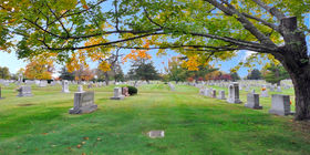 Cemetery grounds with headstones and a flat marker under a tree at Resthaven Memorial Park.