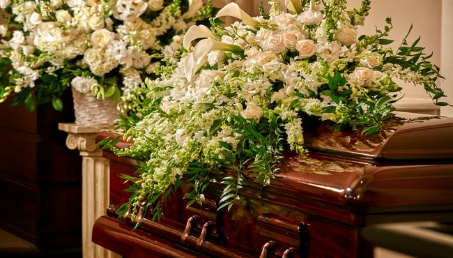 Spray of white roses and tulips laid on top of a wooden casket inside a funeral home.