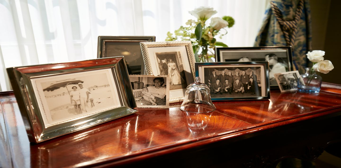 Old images framed and sitting on top of a table near a window inside a funeral home.