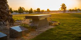 Granite cremation bench and niches in a cemetery at sunset.