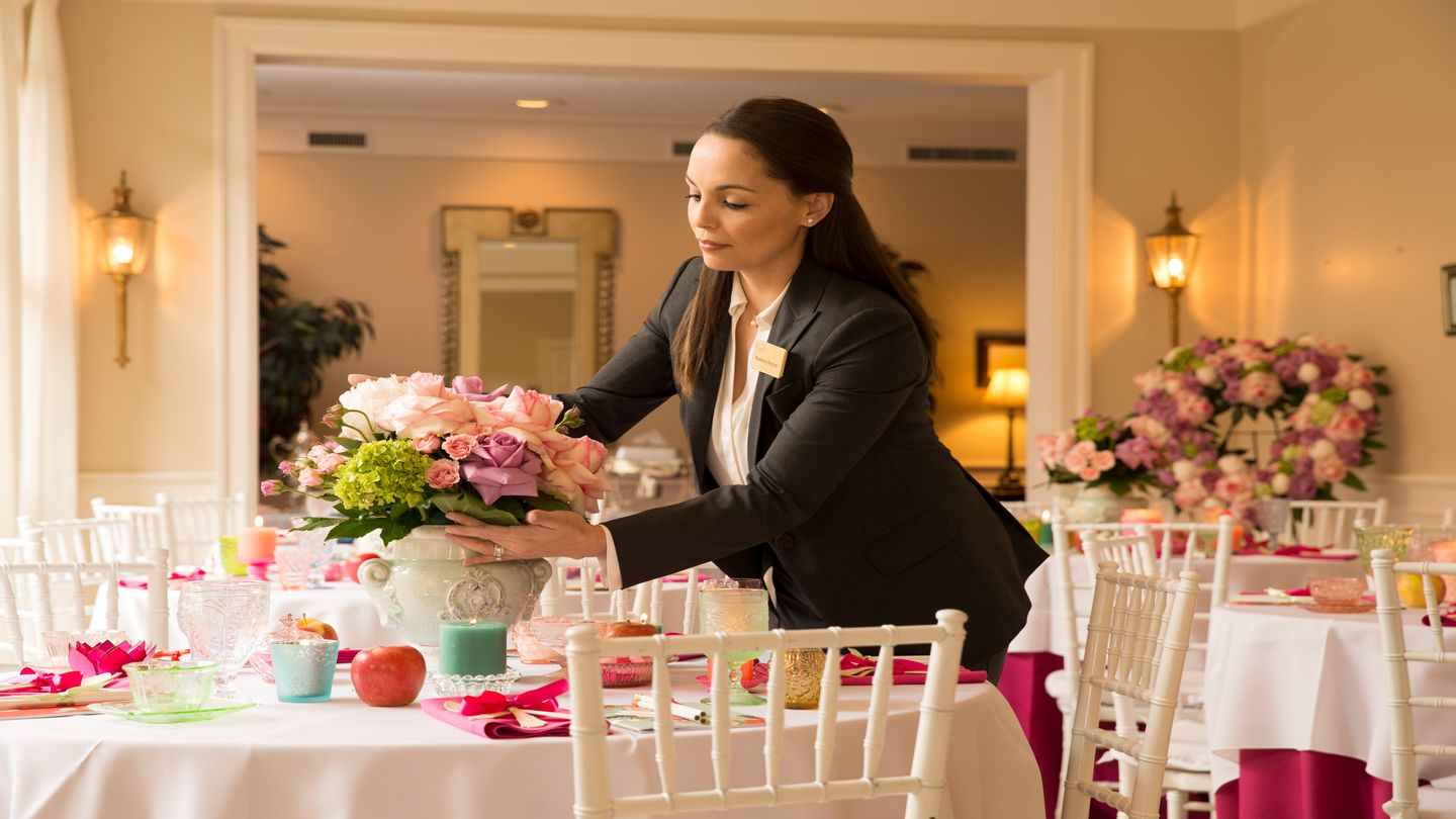 Lady placing floral centerpiece on table.