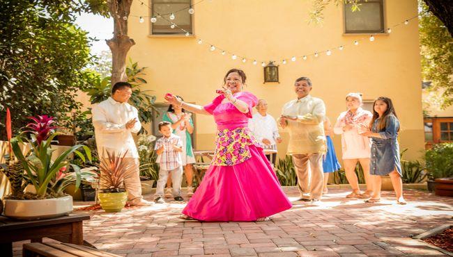 A woman in a fuschia dress performs a dance at an outdoor reception.