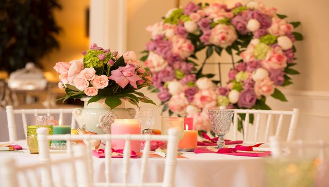 Table setting with floral centerpiece and floral heart wreath in the background.