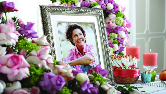 A framed portrait sits among candles, flowers and customized take-away pencils.