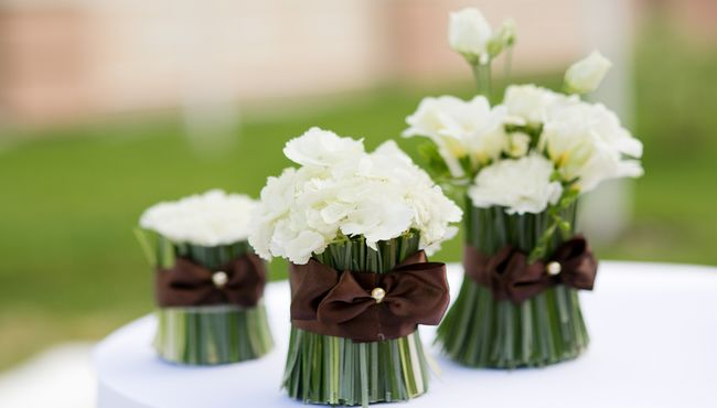 White roses tightly bundled in silky, brown ribbon create a simple and elegant centerpiece.