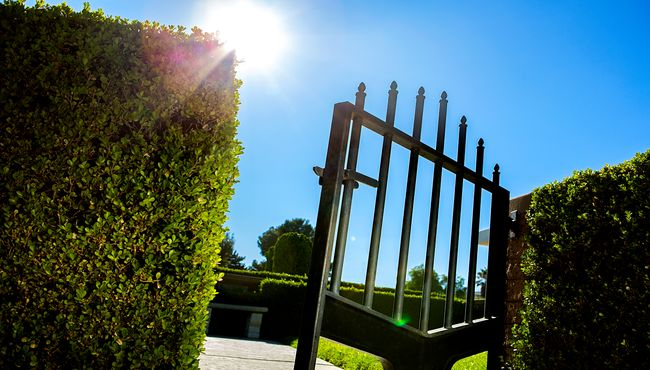 Iron gate leading into a green hedge garden.