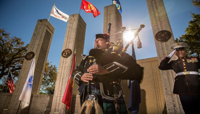 A bagpipe musician plays in front of the Armed Forces flags. A service man salutes behind him.