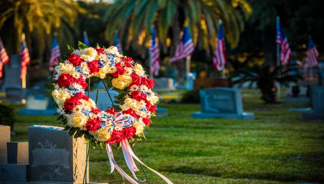 A patriotic floral wreath is displayed in a cemetery with upright markers and American flags