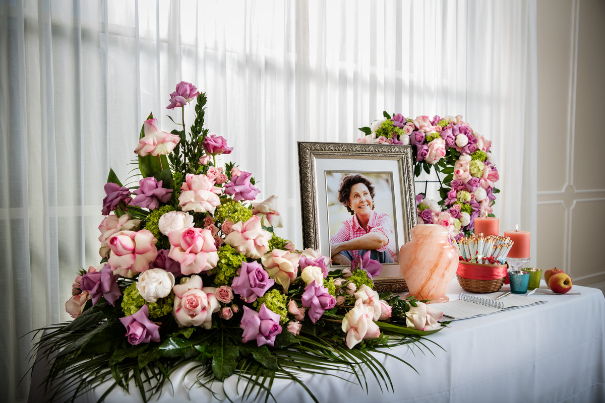 Memorial table with framed photo of older woman and beautiful floral arrangement.