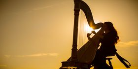 A woman plays the harp at sunset.