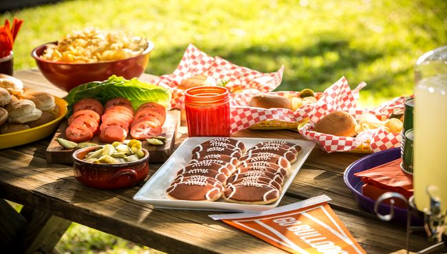 A table of food and beverages at a tailgate celebration.
