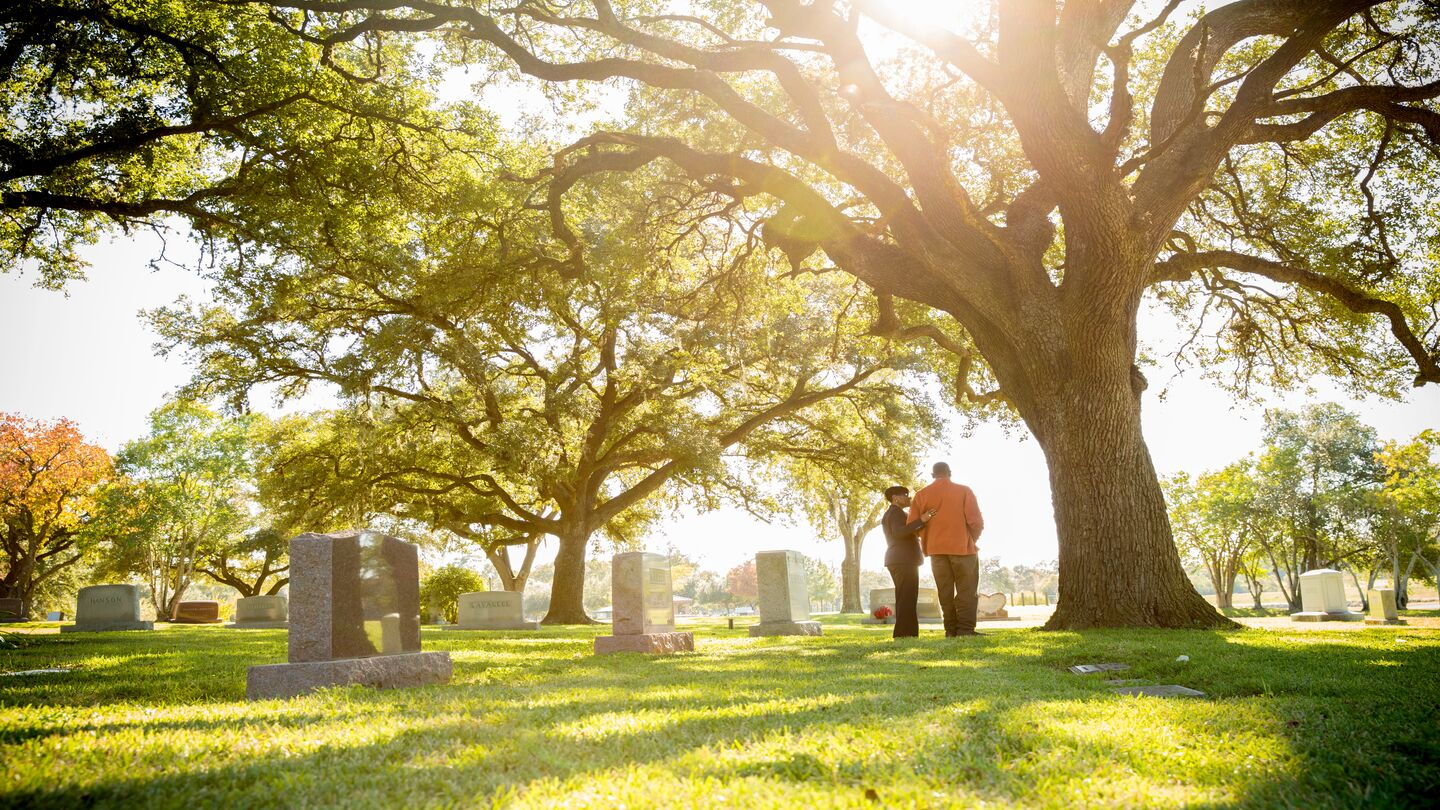 A Dignity Memorial counselor and an African American gentleman standing near a large tree in a cemetery.