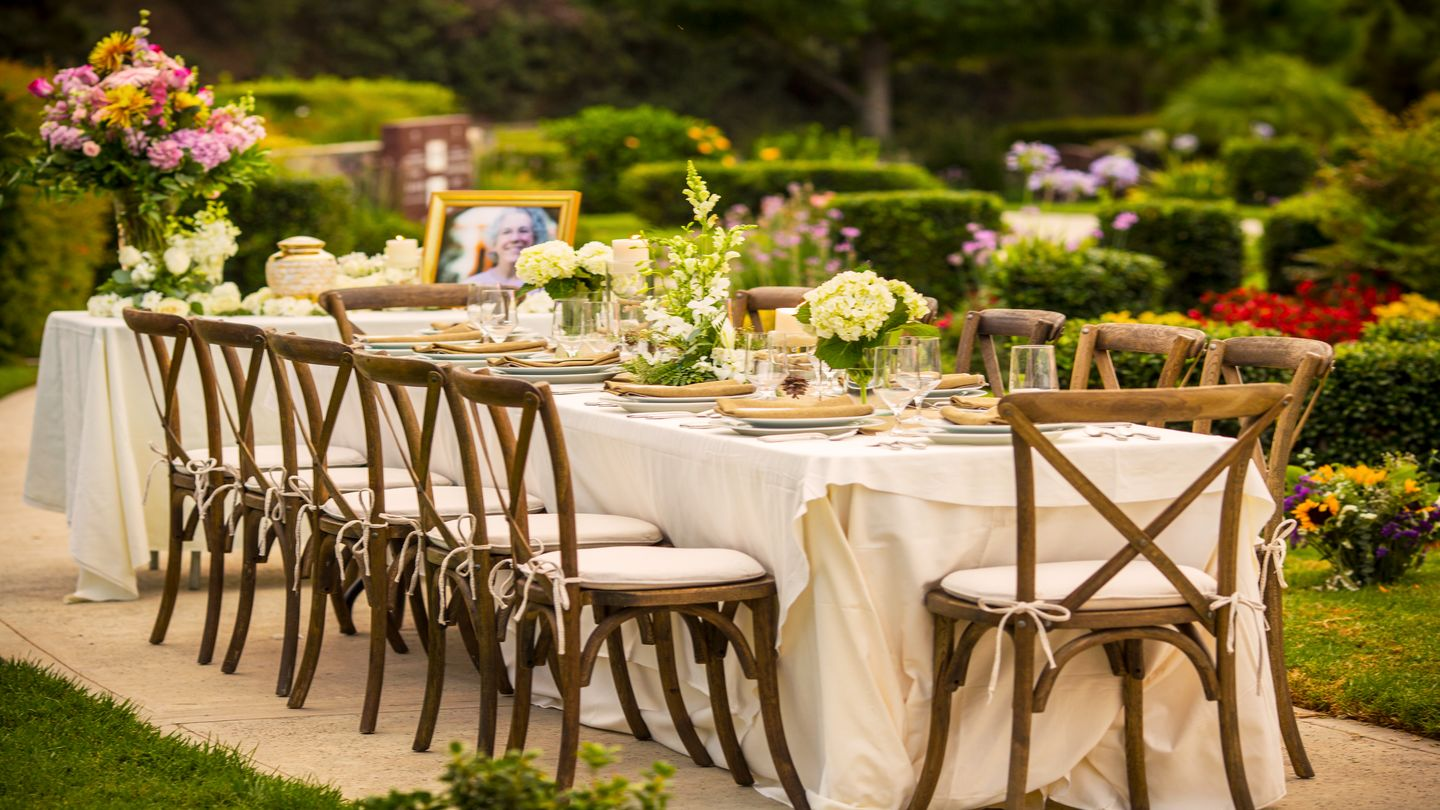 Beautiful outdoor table setting with an urn, portrait and flowers.