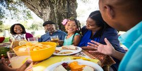 African American family sitting  at table outdoor in cemetery