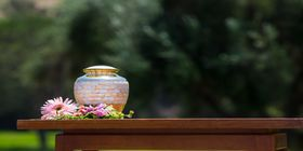 Urn outside on table with flowers around it