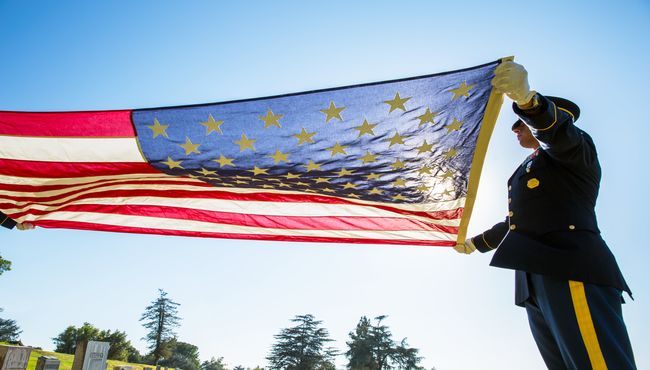 A man in uniform holds an American flag and performs military honors