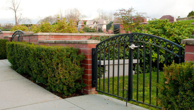 A private, gated family estate garden with red brick walls and a memorial bench.
