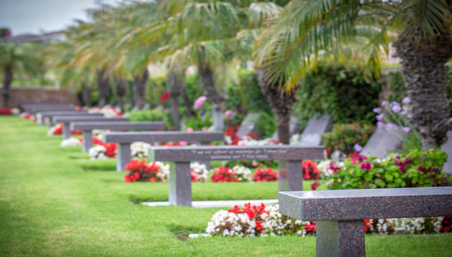 A semi-private garden with memorial benches decorated with red and white flowers at Pacific Vew Memorial Park