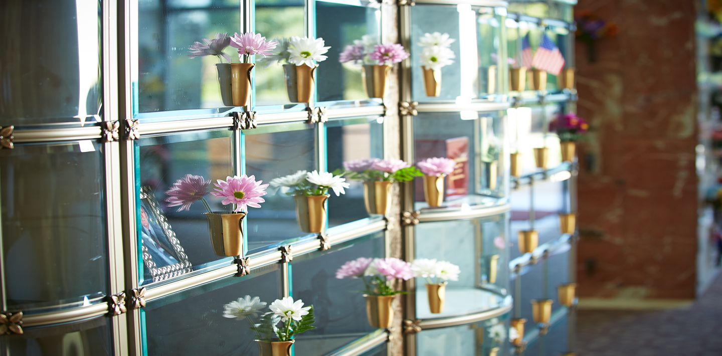 Sunlight illuminates a wall of glass-front cremation niches adorned with pink flowers at Palm Memorial Park.