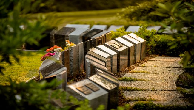 A walkway weaves through natural landscaping along a row of cremation monuments with plaques at Boal Memorial Gardens.