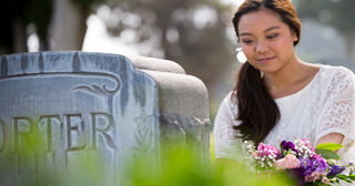 Woman with flowers near headstone