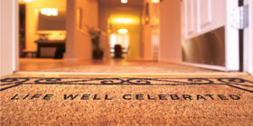 Entryway of a funeral home with a welcome Life Well Celebrated welcome mat.