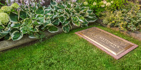 This bronze and granite marker makes a memorable but simple statement amidst well established flora in this private garden.