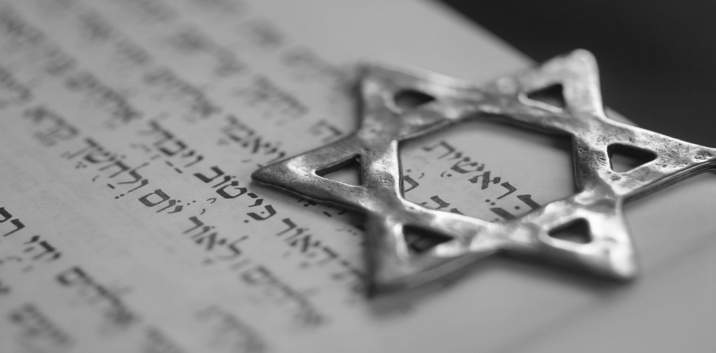 A silver Star of David sits over Hebrew writing.