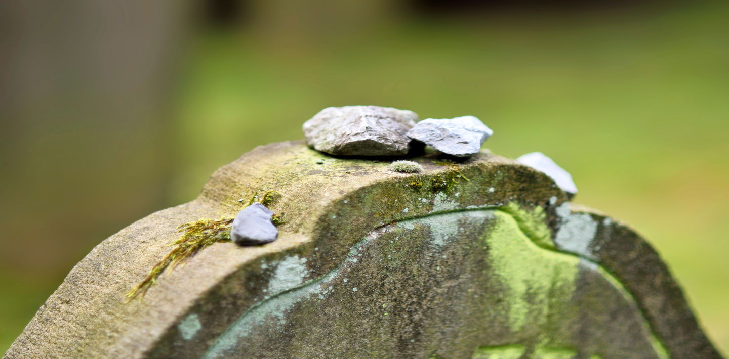 Stones sit on top of a Jewish headstone