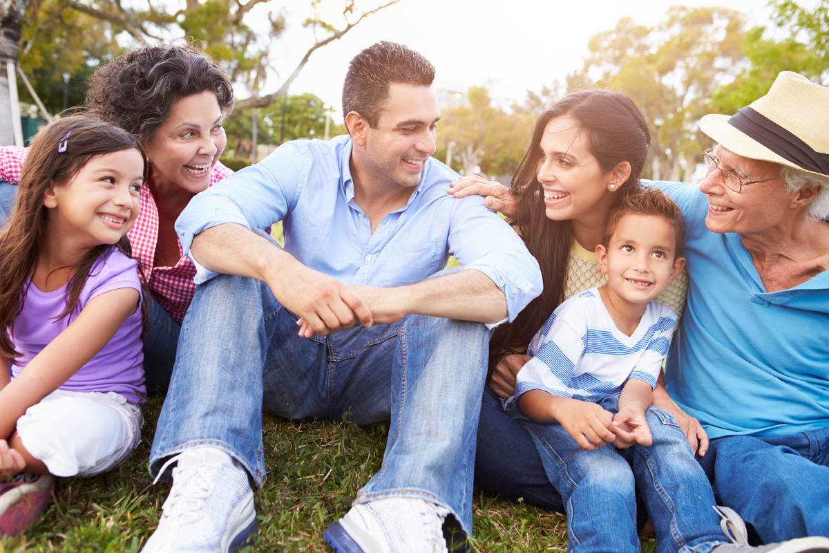 A Hispanic family sitting on the grass together smiling and happy