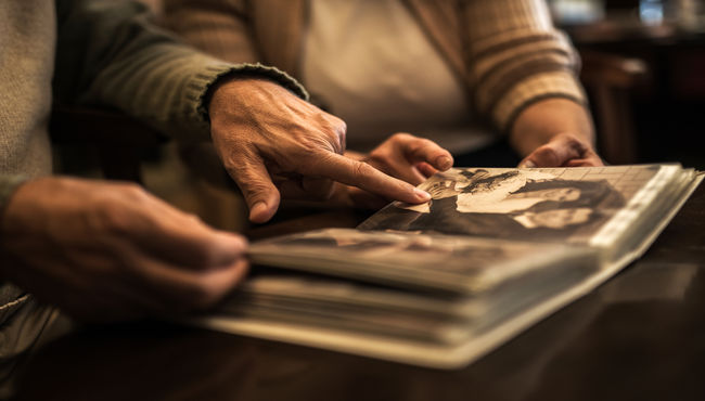 Elderly couple pointing at a wedding photo in photo album.