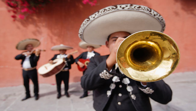 A mariachi band with the trumpet player in front playing music