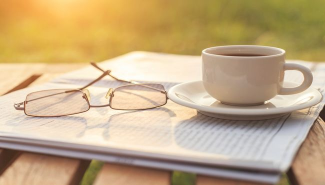 A cup of coffee and eyeglasses rest on a newspaper, representing Father's Day.