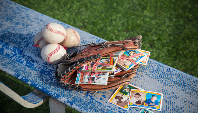 Glove full of baseball cards on a bench nest to a pile of baseballs