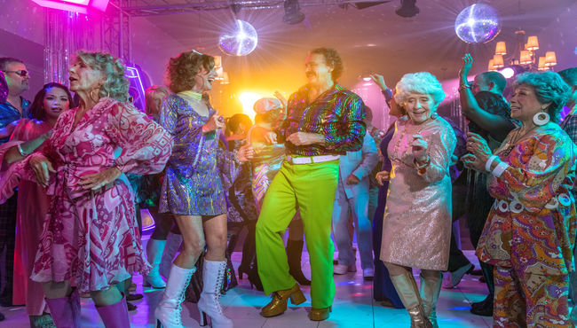 A group of people dancing at a disco-themed memorial
