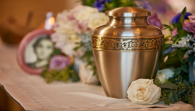 Flower engraved brass urn with a rose beside it sitting on a shelf at Pacific View