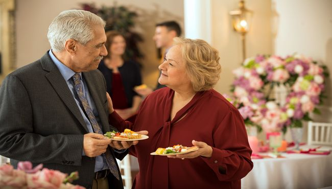 Two guests chat at a decorated catered reception for a teacher
