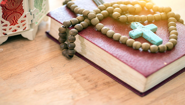 A turquoise rosary laying on a leather bible.