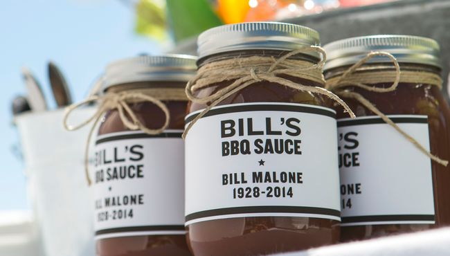 Jars of Bill's BBQ sauce sit on a tray at an outdoor BBQ funeral celebration.