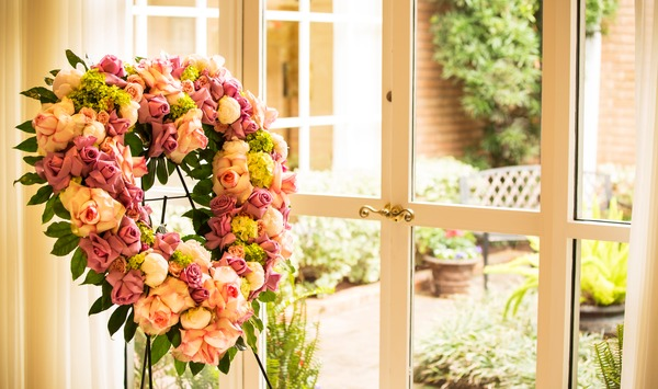 Rose floral heart-shaped wreath on stand facing window.