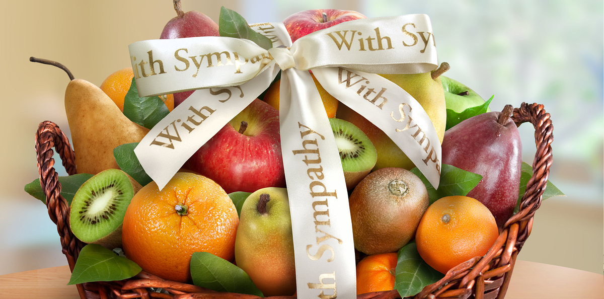 A sympathy gift basket with various fruits.
