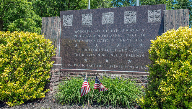 This granite monument dedicated to Veterans and their families reads 'Patriotic Sacrifice Forever Remembered' at Highland Park Cemetery & Mausoleum